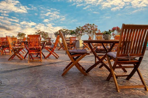 Terraza exterior de un café con sillas y mesas de madera vacías sobre un fondo de cielo azul al atardecer