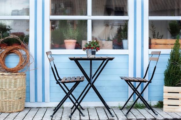Terraza de invierno con cestas de mimbre y plantas verdes en macetas en el porche de la casa.