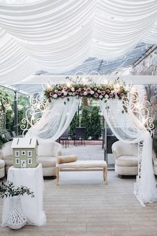 Terraza luminosa de boda al aire libre con arco floral