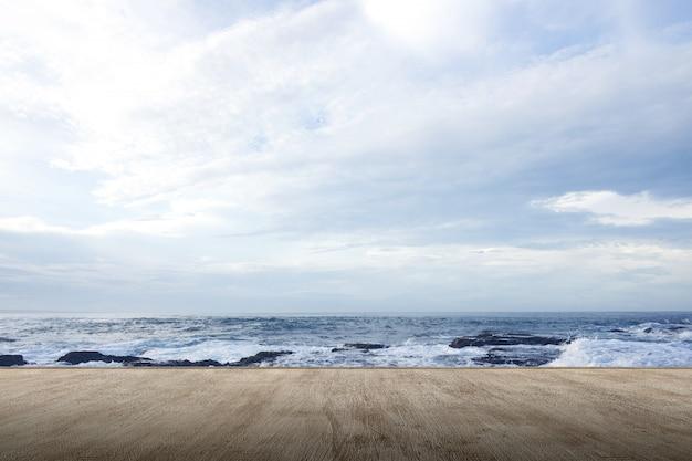 Terraza de madera con vista al mar y olas.