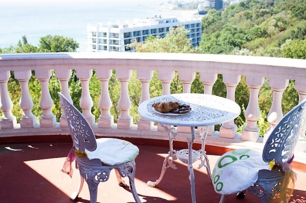 Terraza con sillas y una mesa con una hermosa vista al mar