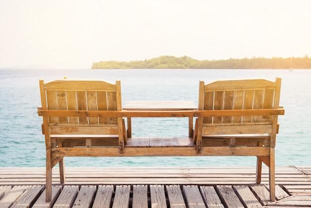 Terraza vista al mar con mesa y sillas de madera al aire libre.