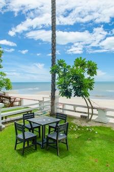 Terraza con vistas al mar con mesa y sillas de madera.