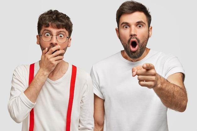 Terrifc dos chicos con expresión asustada, notan algo horrible al frente, se paran muy cerca el uno del otro, vestidos con camisetas blancas casuales. jóvenes caucásicos sin afeitar reaccionan ante algo terrible