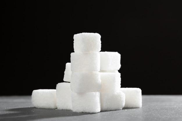 Terrones de azúcar apilados juntos contra un fondo negro