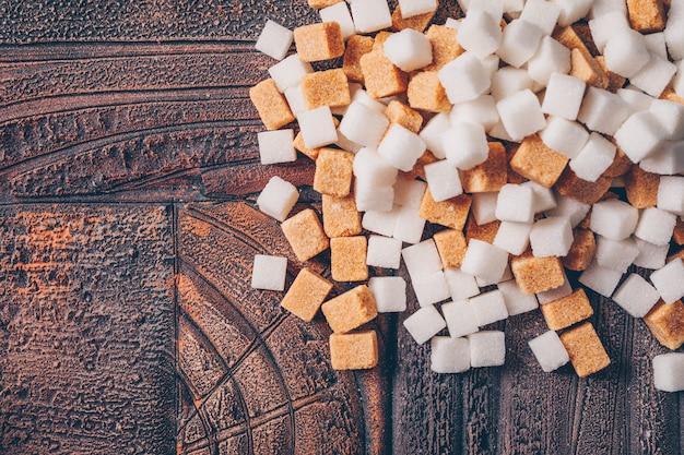 Terrones de azúcar blanco y marrón sobre una mesa de madera oscura. vista superior.