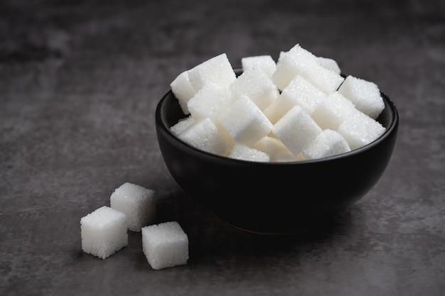 Terrones de azúcar blanco en un recipiente en la mesa.