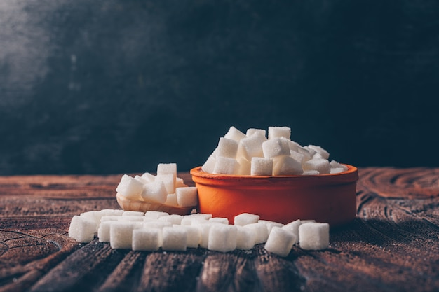Terrones de azúcar blanco en un tazón de naranja con vista lateral de cuchara sobre una mesa oscura y de madera