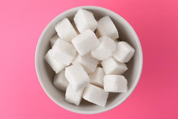 Terrones de azúcar en un bol en rosa