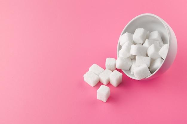 Terrones de azúcar en un tazón sobre fondo rosa