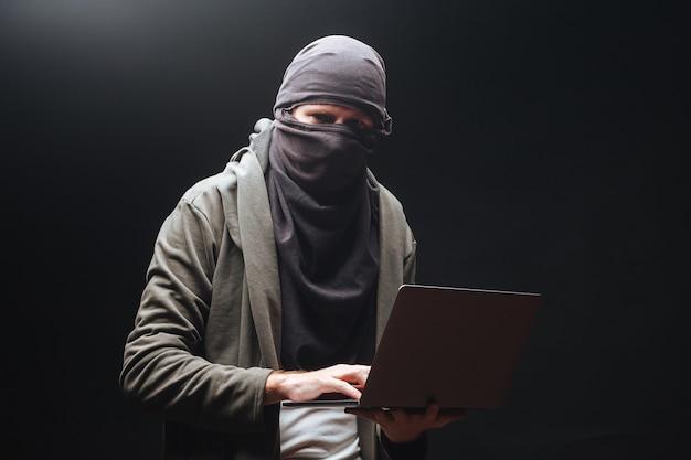 Un terrorista con una computadora portátil está preparando un crimen por la noche.