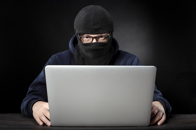 Terrorista en máscara y gafas sentado en un portátil en una pared oscura