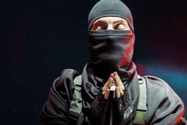 Terrorista rezando con un libro en sus manos