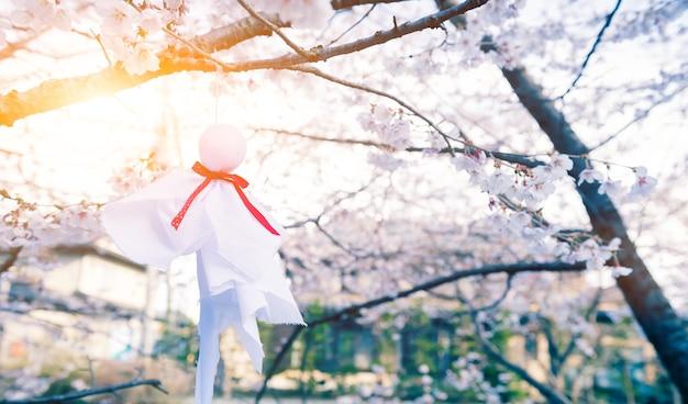 Teru teru bozu. muñeca de lluvia japonesa colgada del árbol de sakura para orar por el buen tiempo
