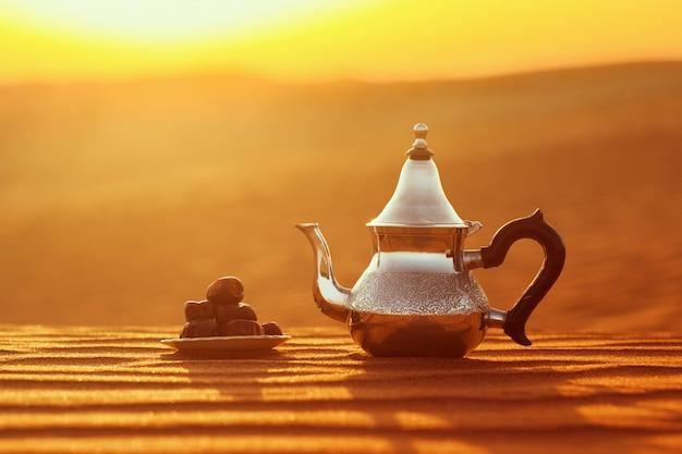 Tetera árabe y fechas en el desierto en una hermosa puesta de sol que simboliza el ramadán