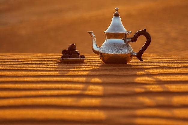 Tetera árabe y fechas en el desierto en una hermosa puesta de sol