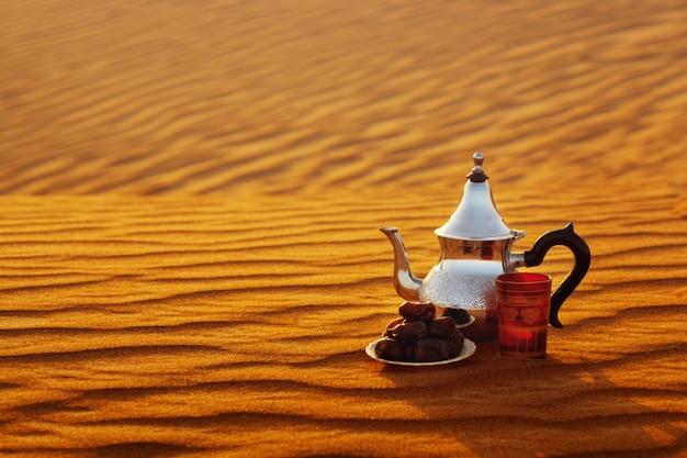 Tetera árabe, taza y dátiles sobre la arena en el desierto