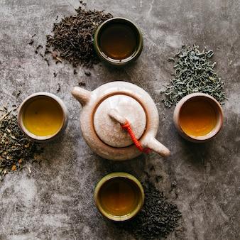 Tetera de barro cerámico con hierbas secas de té y tazas de té sobre fondo oscuro