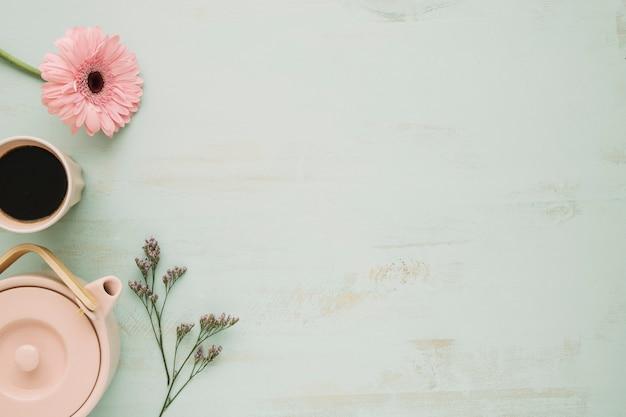 Tetera y bebida cerca de las flores