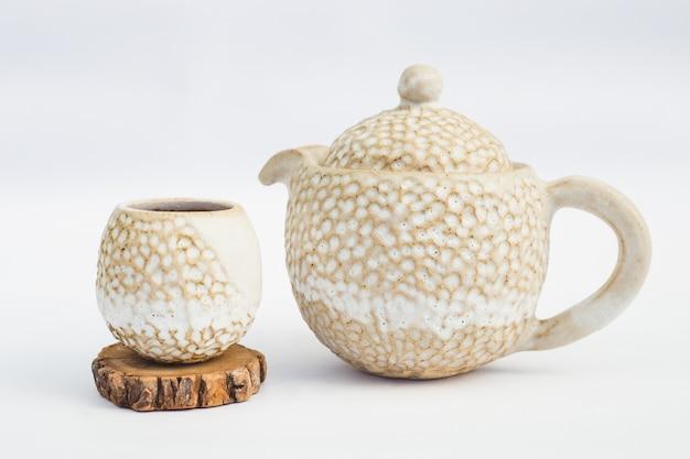 Tetera beige y taza de gres cerámico con fondo blanco