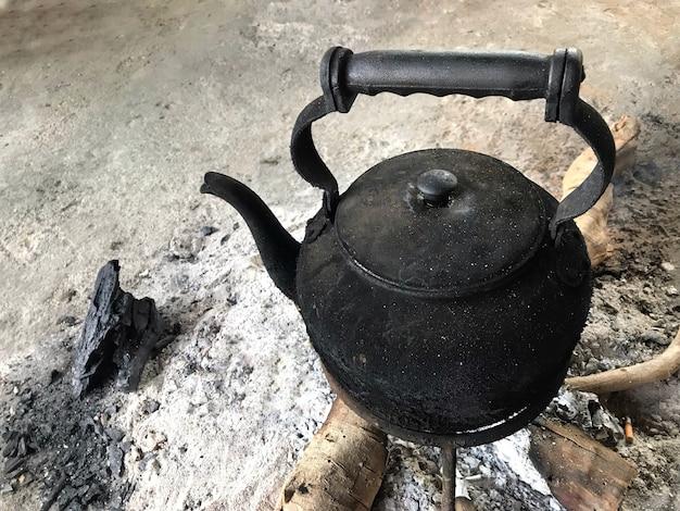 Tetera caliente del negro tailandés quemado del vintage en la madera de los carbones de leña del fuego.