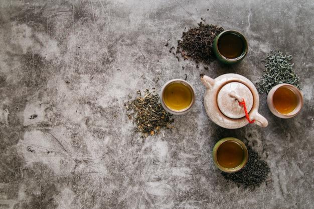 Tetera de cerámica rodeada de hierbas secas y tazas de té sobre fondo de hormigón