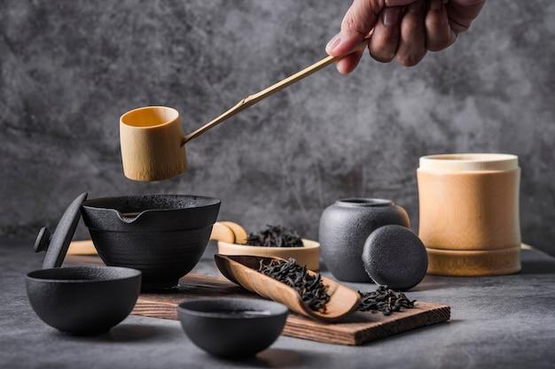 Tetera de cerámica y tazas con hierbas negras