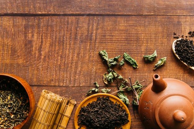 Tetera china tradicional con hojas de té y mantel individual sobre escritorio de madera