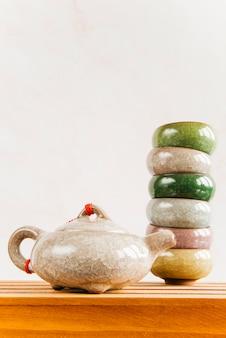 Tetera china tradicional con una pila de tazas de té en la mesa de madera