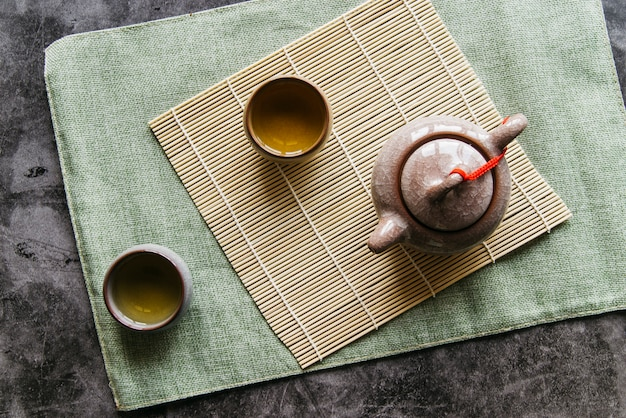 Tetera china tradicional y tazas de té en mantel sobre la servilleta