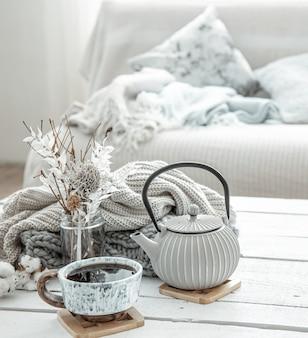 Una tetera y una hermosa taza de cerámica con detalles decorativos en una sala de estar estilo hygge