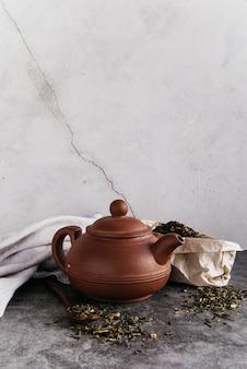 Tetera de hierbas verdes con hojas de té secas con servilleta contra la pared