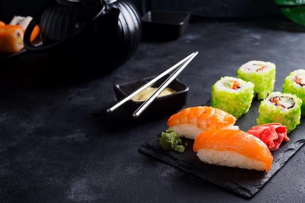 Tetera de hierro negro y sushi en placa de pizarra en mesa de piedra negra