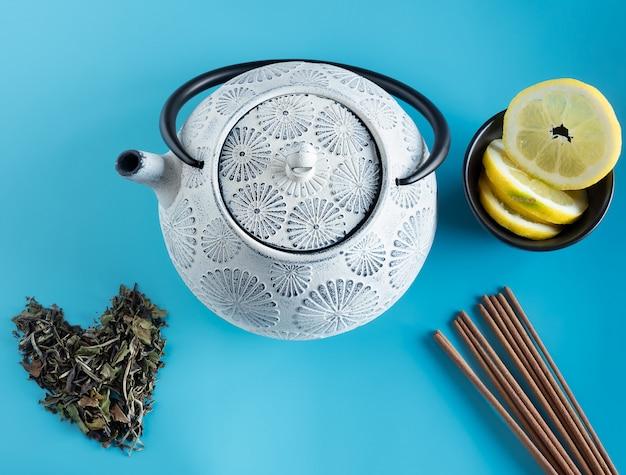 Tetera de hierro en tonos azul y negro con hojas de té verde, cuenco marrón, rodajas de limón y palitos en barritas