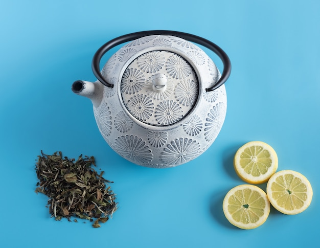 Tetera de hierro en tonos azules y negros, acompañada de hojas de té verde y gajos de limón