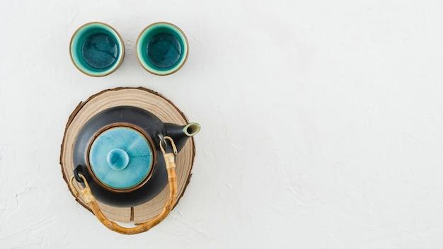Tetera de loza de barro con tazas de té aisladas sobre fondo blanco