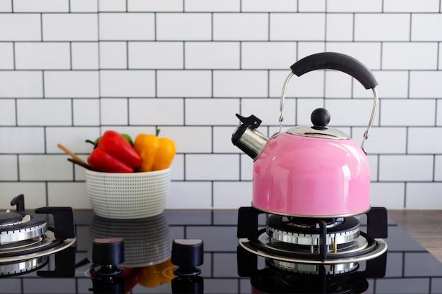 Tetera de metal rosa en la cocina.
