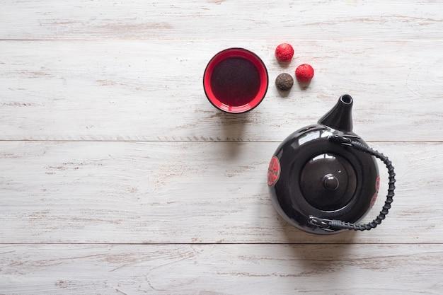 La tetera negra de té chino y la taza roja con té están sobre la mesa de madera blanca.