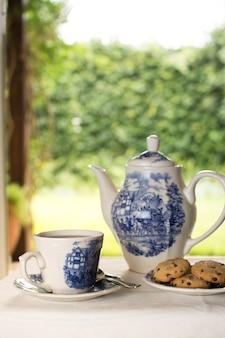 Tetera de porcelana y tazas de té con galletas en forma de ballena en la mesa al aire libre