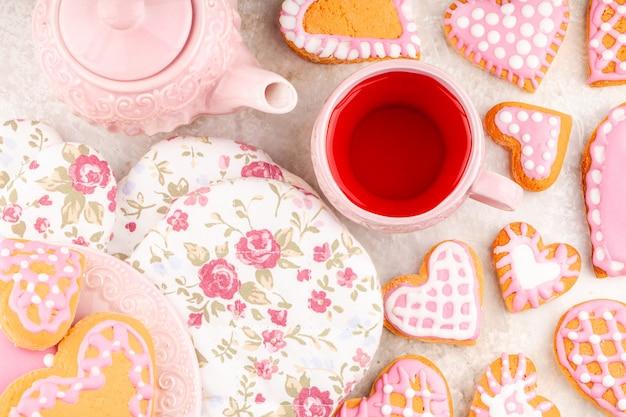 Tetera rosa con taza, guantes de flores y plato de galletas hechas a mano en forma de corazón