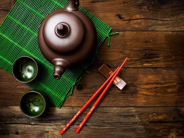 Tetera sobre estera de bambú verde. vista superior