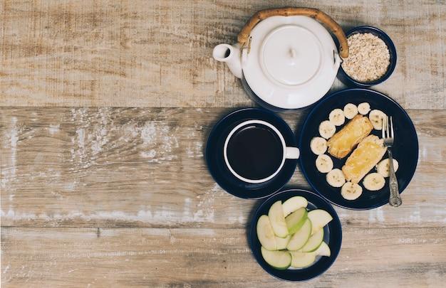 Tetera; taza de café y desayuno saludable sobre fondo con textura de madera