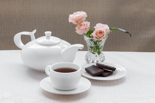 Tetera, taza, rosas y chocolate en un plato