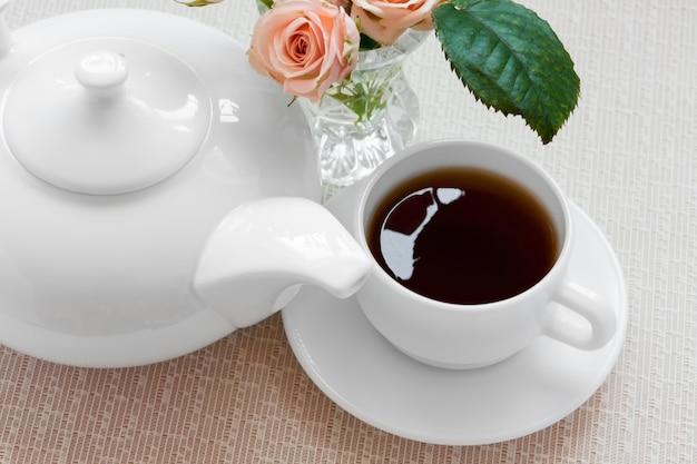 Tetera, taza y rosas en un plato