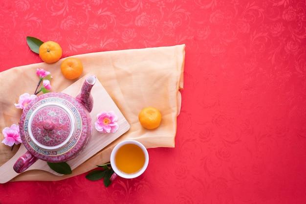 Tetera y taza de té con flor de cerezo sobre fondo rojo