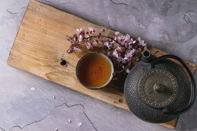Tetera y taza de té con rama de flor