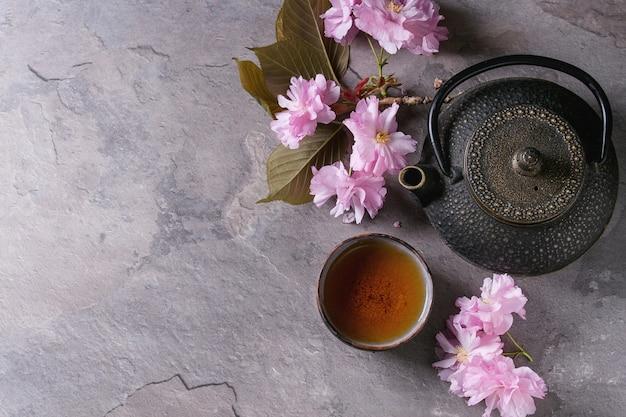 Tetera y taza de té con rama flor.