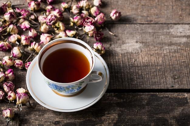 Tetera y taza de la vendimia con las flores florecientes del té en de madera