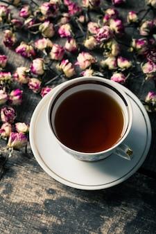 Tetera y taza de la vendimia con las flores florecientes del té en la madera
