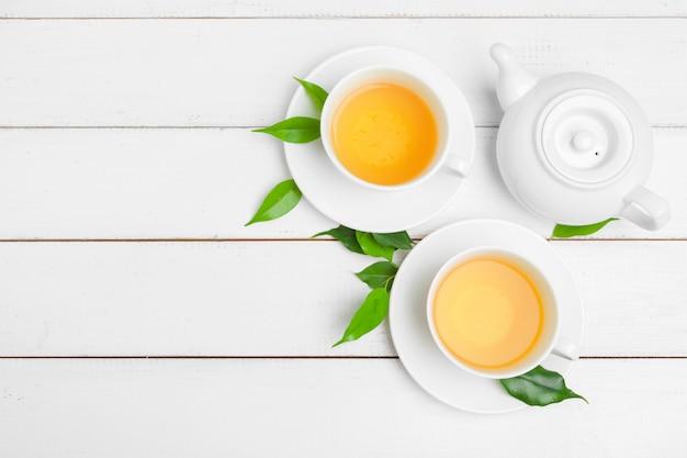 Tetera y tazas de té sobre un fondo blanco de madera